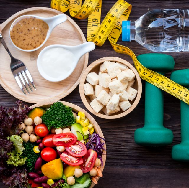 fresh vegetable salad and healthy food for sport equipment for women diet slimming with measure tap for weight loss on wood background healthy sport concept