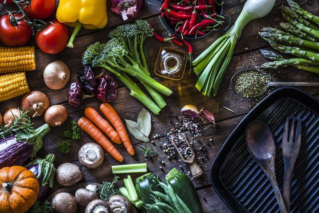fresh vegetables ready for cooking shot on rustic wooden table