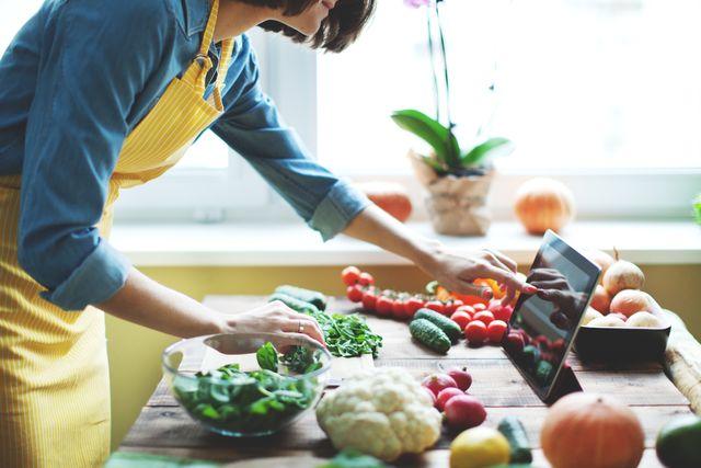 donna guarda ricette su tablet su tavolo con verdure