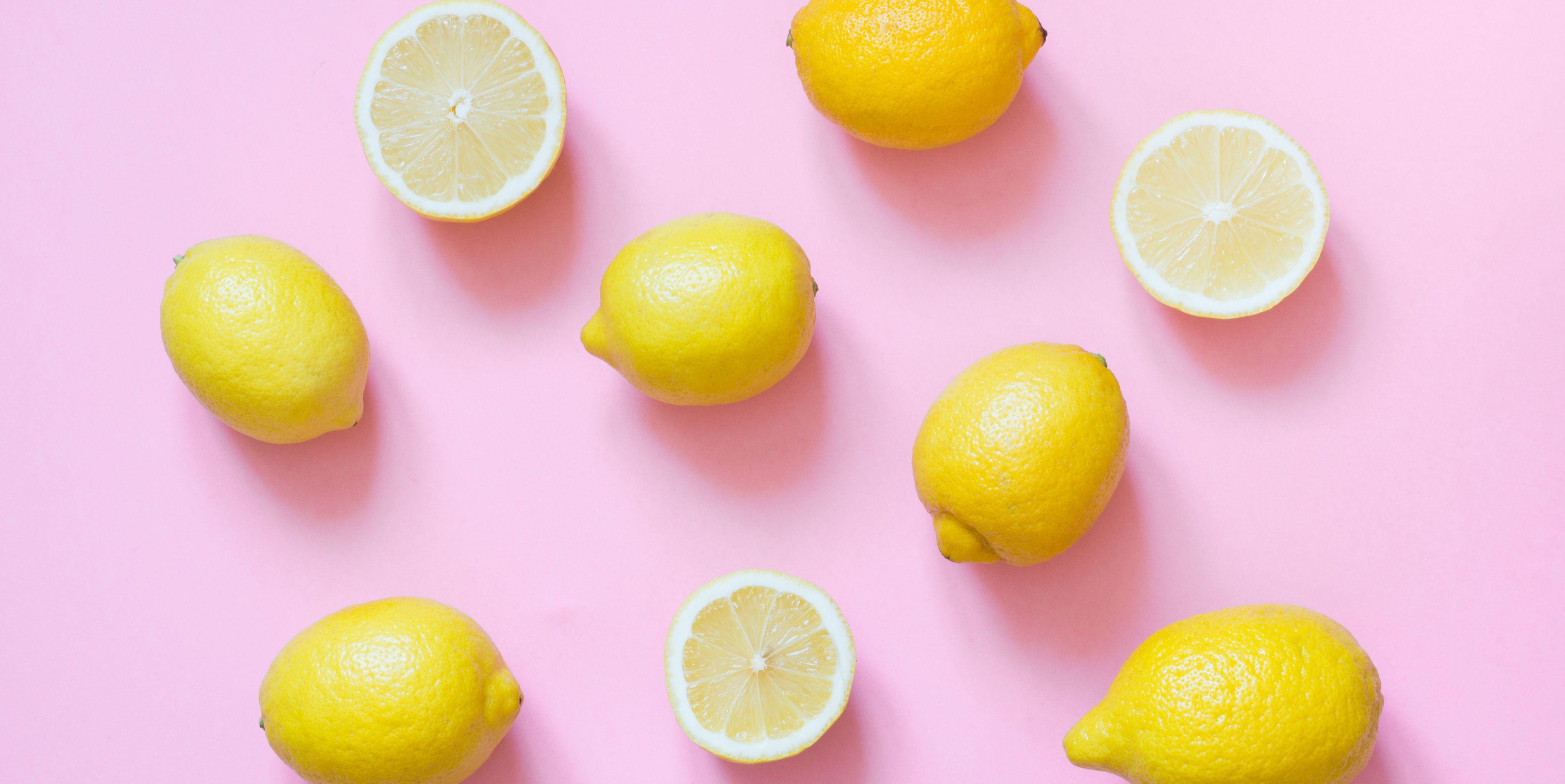 Fresh whole and sliced lemon on pink background. Flat lay.