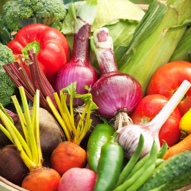subject a basket of varieties of freshly harvested summer garden produce vegetables including broccoli, garlic, green beans, radishes, purple cabbage, red bell peppers, heirloom tomatoes, carrots, zucchini, squash, purple onions and corn