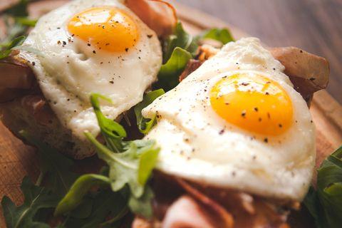 Fried eggs sunny side up on baguette, ham and arugula