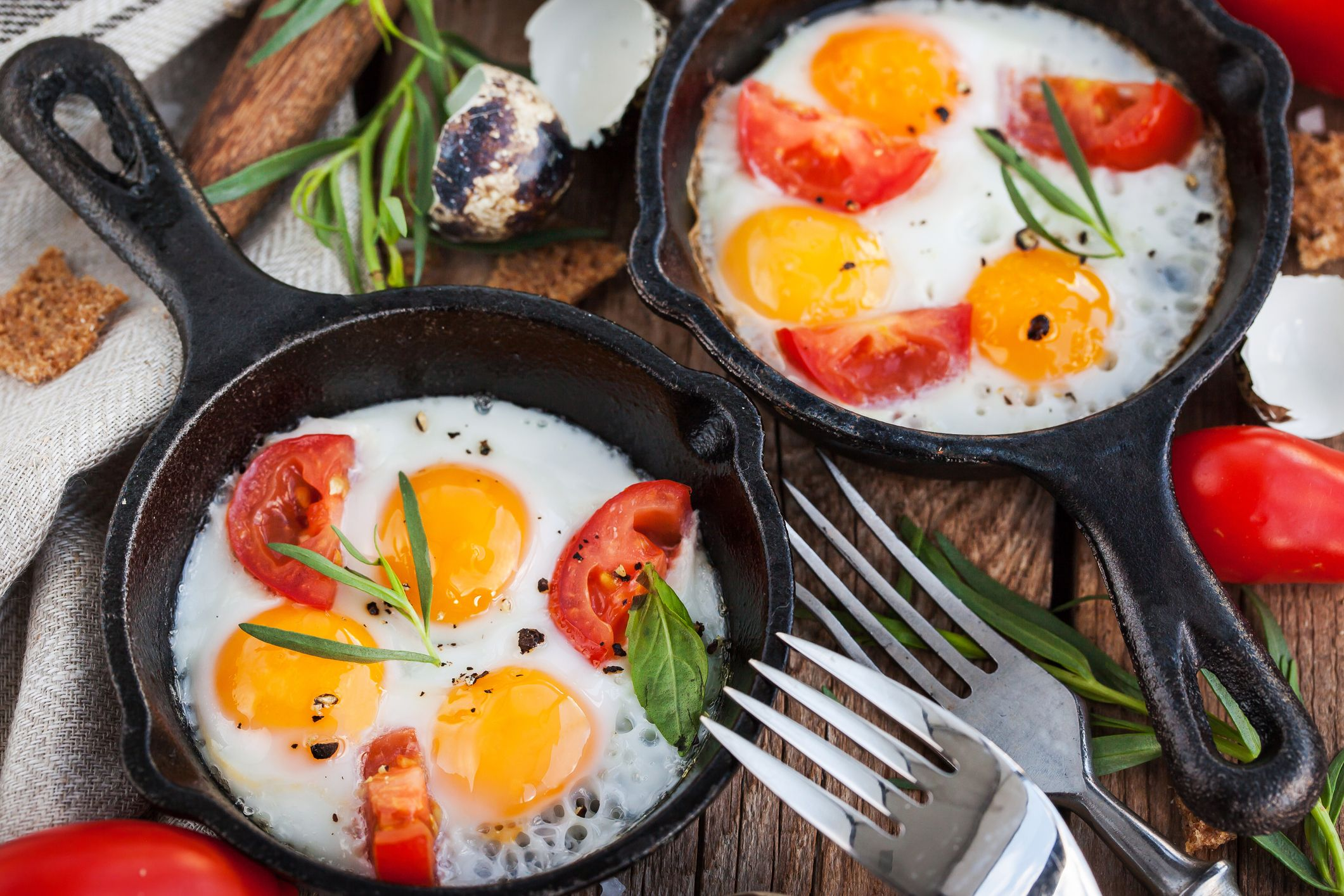Fried eggs with tomatoes in frying pans served for breakfast