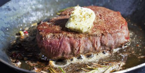 Fried fillet of beef with herb butter, peppercorns and rosemary in a pan