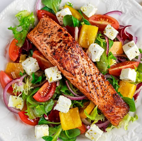 Fried Salmon steak with fresh vegetables salad, feta cheese. concept healthy food.