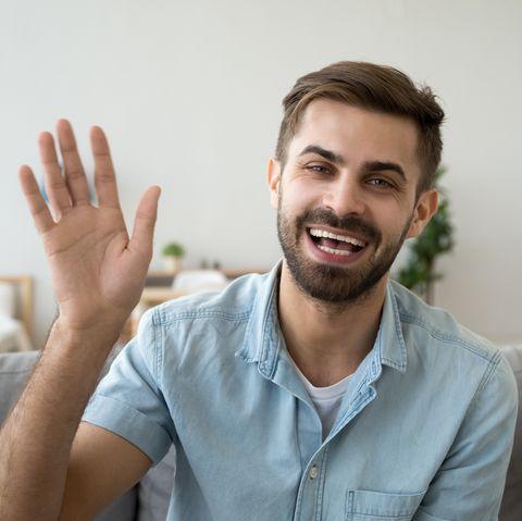 friendly happy man waving hand saying hello looking at camera