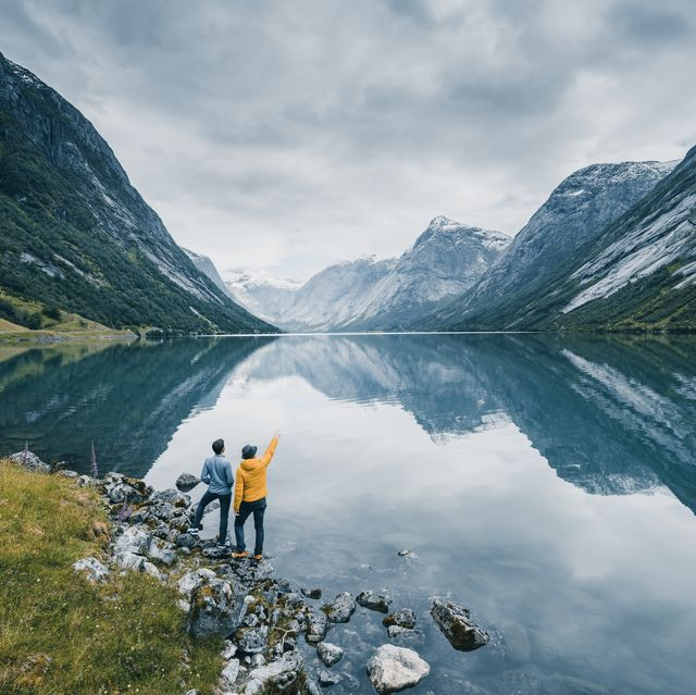 friends admiring the view on the banks of a norwegian fjord, norway