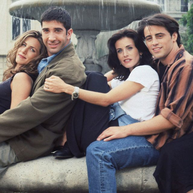 friends cast sitting together next to fountain