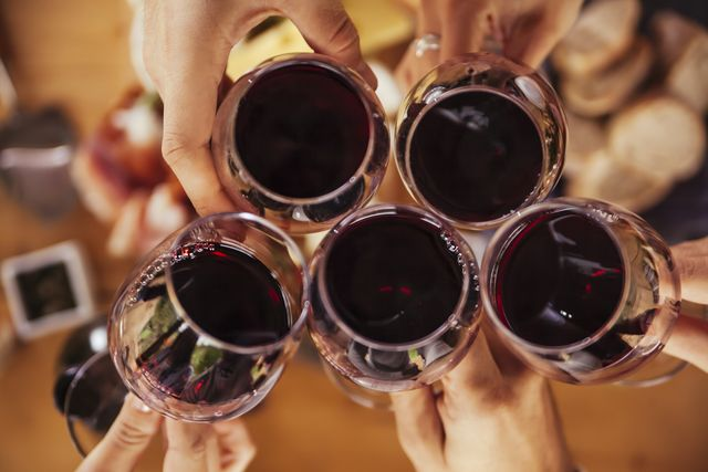 friends clinking red wine glasses