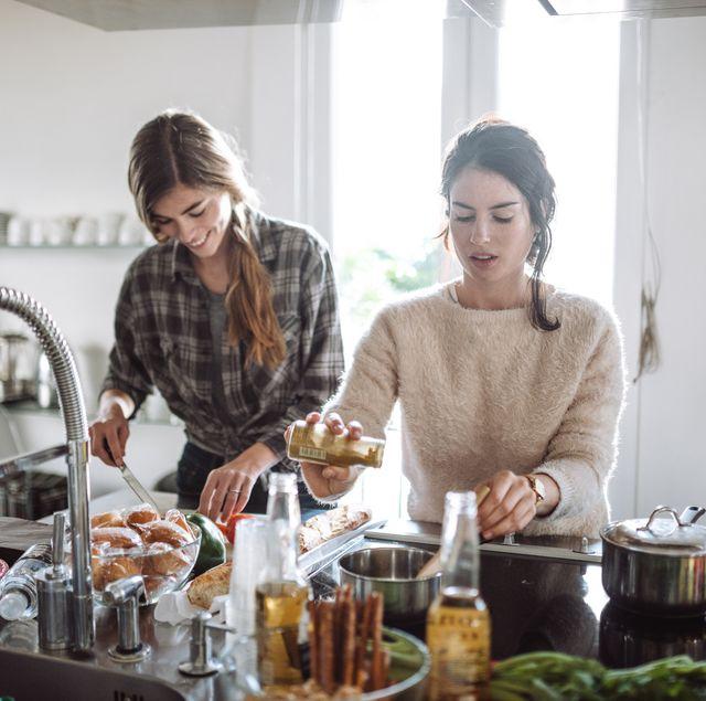 twee vrouwen staan in de keuken te koken