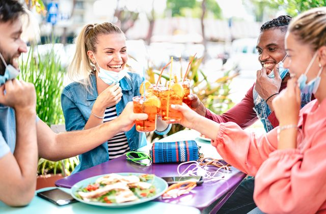 friends drinking spritz at cocktail bar with face masks   new normal friendship concept with happy people having fun together toasting drinks at restaurant   bright filter with focus on left woman