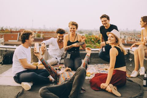friends enjoying music on speaker during rooftop party at terrace against sky