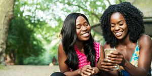 Friends laughing sharing on smart phone.