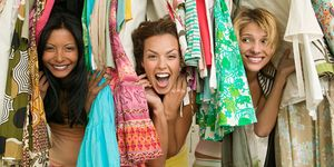 Women clearing out wardrobe and laughing