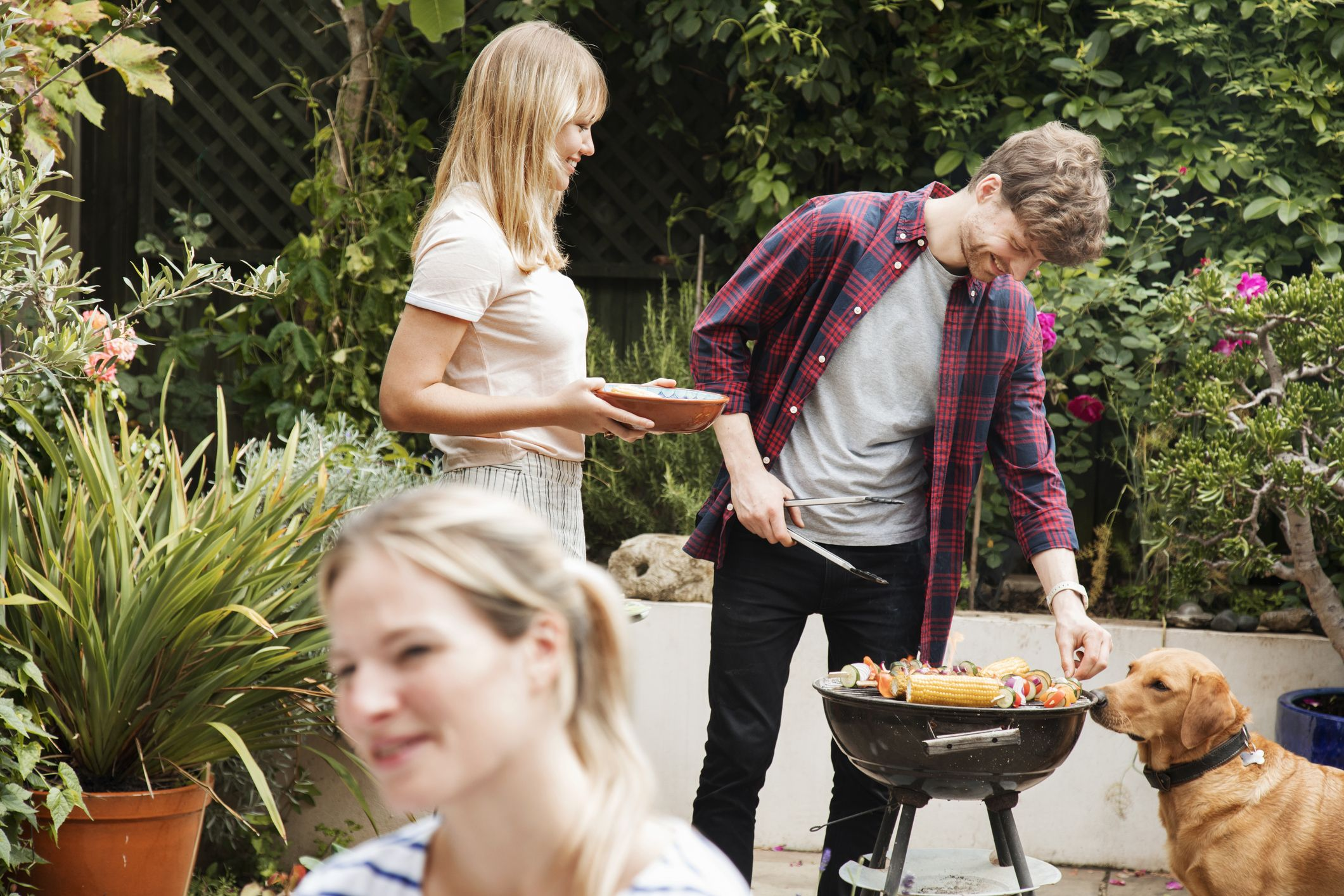 Friends prepare food on barbecue while dog looks on at garden party