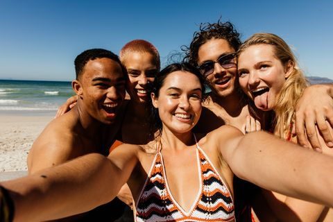 Friends taking a selfie of themselves on the beach