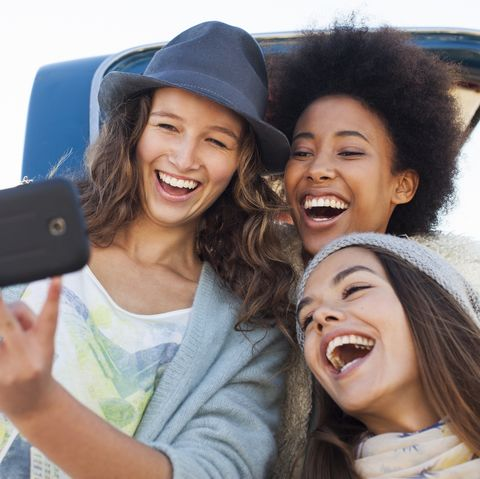 Friends taking photo with mobile phone by truck