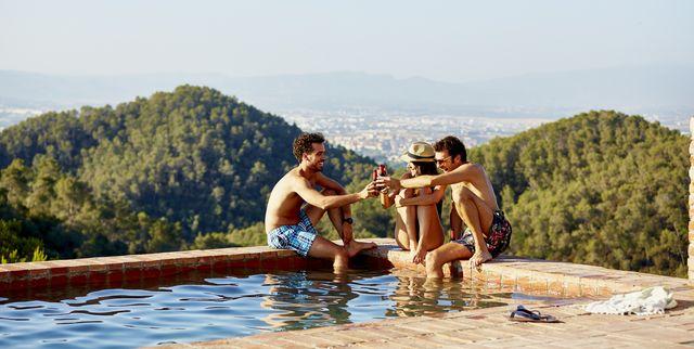friends toasting beer bottles at pool's edge