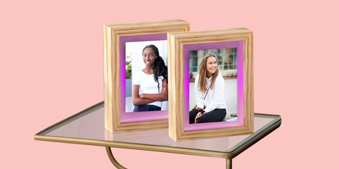 two light up picture frames on glass table with pink background