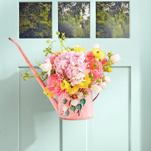 arrangement of flowers in a pink watering can hanging on a front door