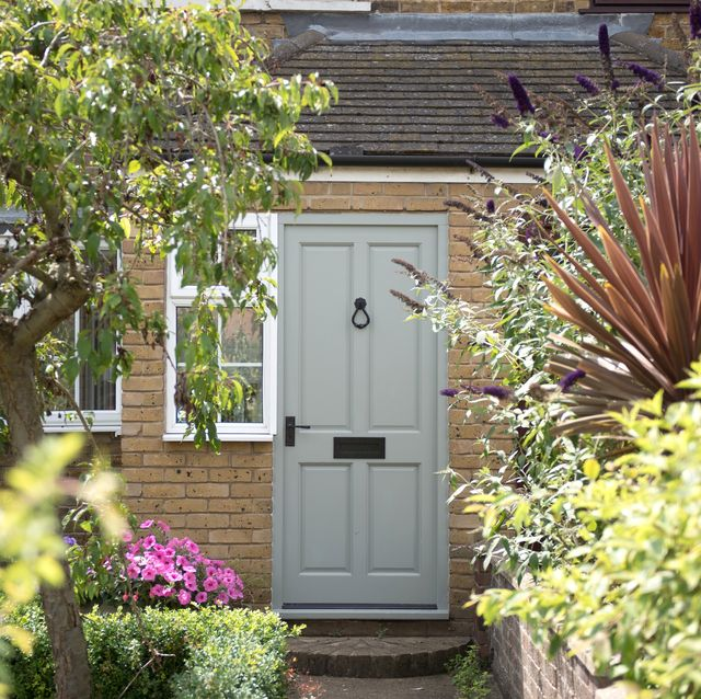 a general exterior view of a sage green front door of a house with a white picket gate of a home
