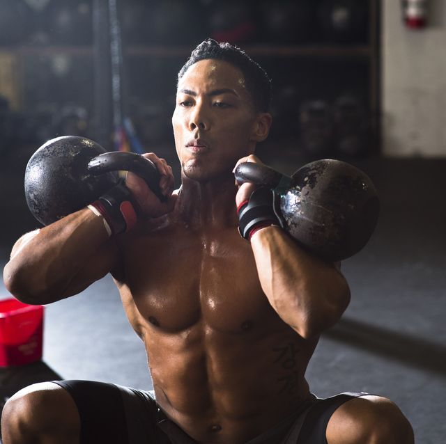 Front view of athlete doing kettle bell squats, San Diego, California, USA