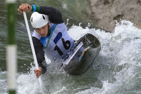 Front View of Young Male Canoeist in the Whitewater Reaching the Green Gate