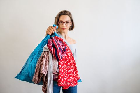a front view portrait of woman indoors holding bag with old clothes