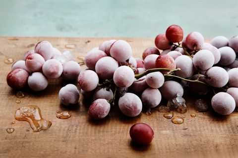 Frozen red grapes on wooden chopping board