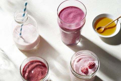 Fruit and yogurt smoothies in glass bottle and jars, overhead view