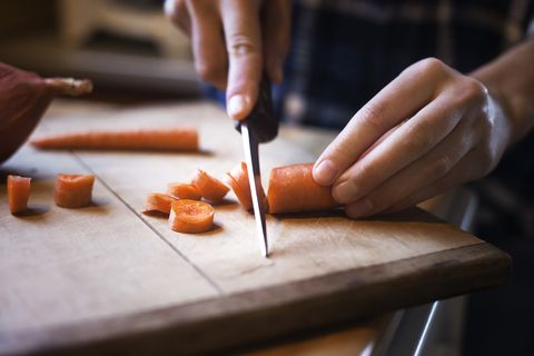 Close-up of woman chopping carrot on cutting board
