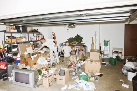 Frustrated father and son cleaning clutter in garage