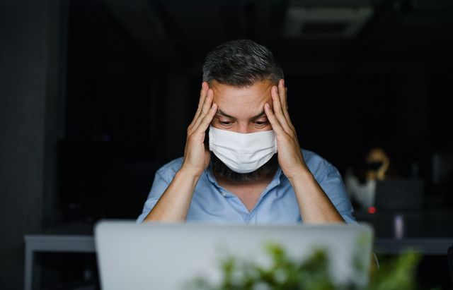frustrated mature man with face mask sitting indoors in office, working