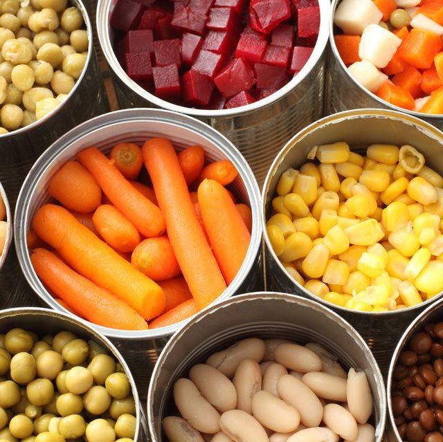 varias latas con diferentes frutas, verduras y alubias