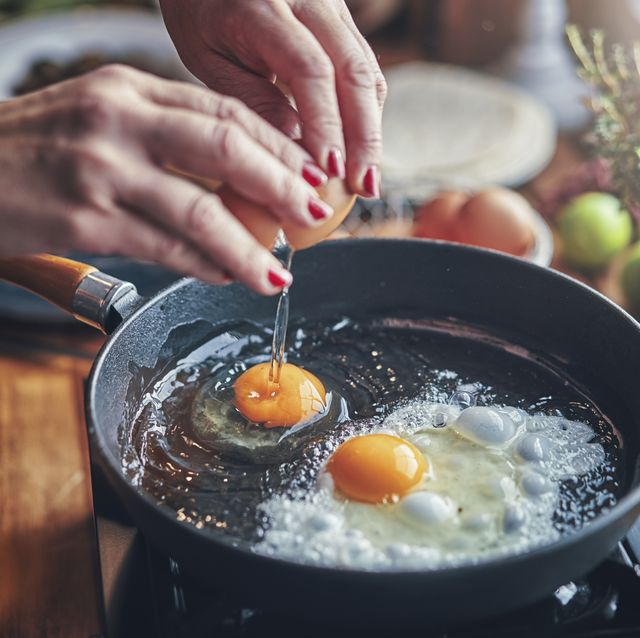 frying egg in a cooking pan in domestic kitchen