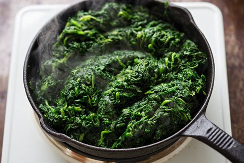 Frying thawed frozen spinach on iron skillet