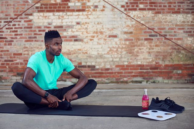 man sitting cross legged next to his fittrack scale