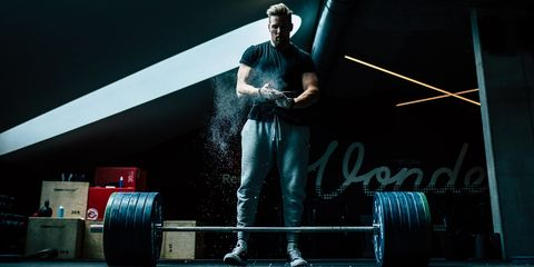 Man smeert kalk over handen uit door in handen te klappen,voordat hij gaat deadliften in een donkere sportschool.