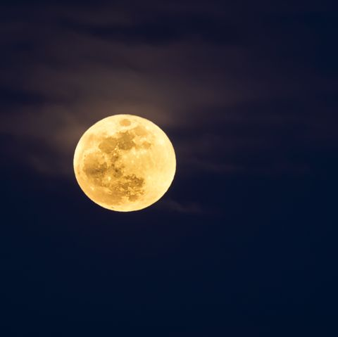 Full frame of the Supermoon of yellow color on a black sky with some high clouds. Valencia, Spain