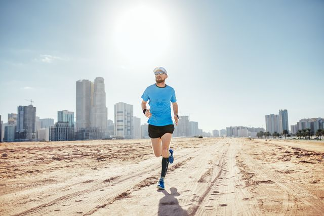 full length front view of mid adult man running on sand by sky scrapers, dubai, united arab emirates
