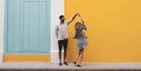 Full Length Of Couple Dancing On Sidewalk Against Yellow Wall