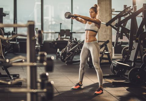 Full length of determined sportswoman exercising with kettle bell in a gym.