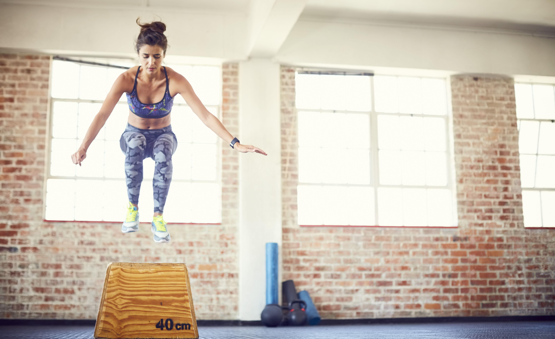 Full length of fit female athlete jumping over box