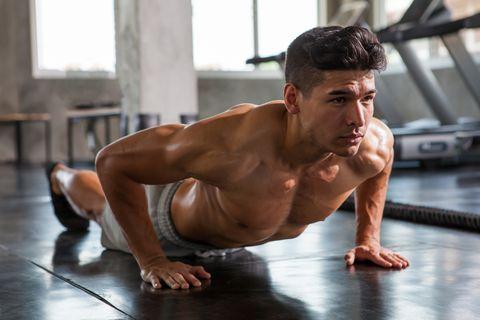 Full Length Of Male Athlete Doing Push-Ups In Gym