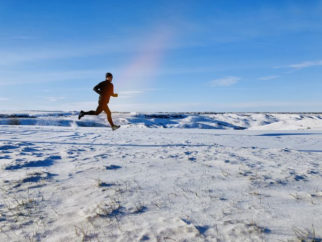 full length of man running in snow covered land against sky