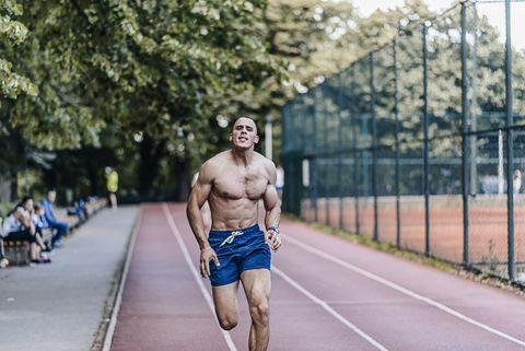 full length of shirtless man running in park