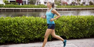 Full length of sporty mature woman running on footpath