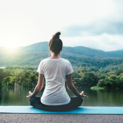 Full Length Of Woman Doing Yoga Against Lake