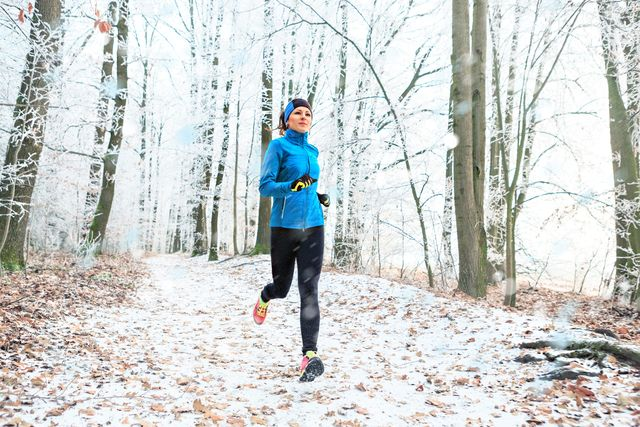 full length of woman jogging in forest during winter