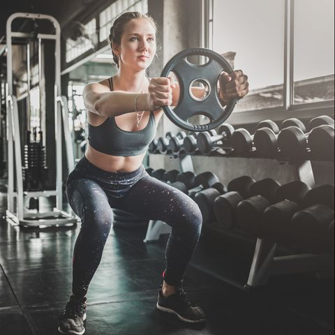 Full Length Of Woman Lifting Weight In Gym